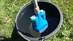 mobile Campingdusche hängt in einen Eimer mit Wasser